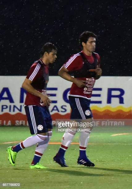 Paraguay's national football team players Oscar Romero and Cristian Riveros take part in a training session at the Complejo Albiroga training centre...