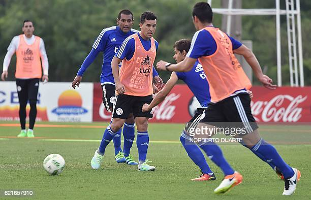 Paraguay's national footballers Paulo Da Silva Juan Patino and Oscar Romero vie for the ball during a training session at the Complejo Albiroga...