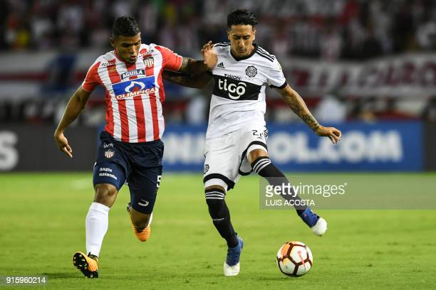 Paraguay's Olimpia midfielder Santiago Rosales of Argentina vies for the ball with Colombian Junior defender Rafael Perez during their Copa...