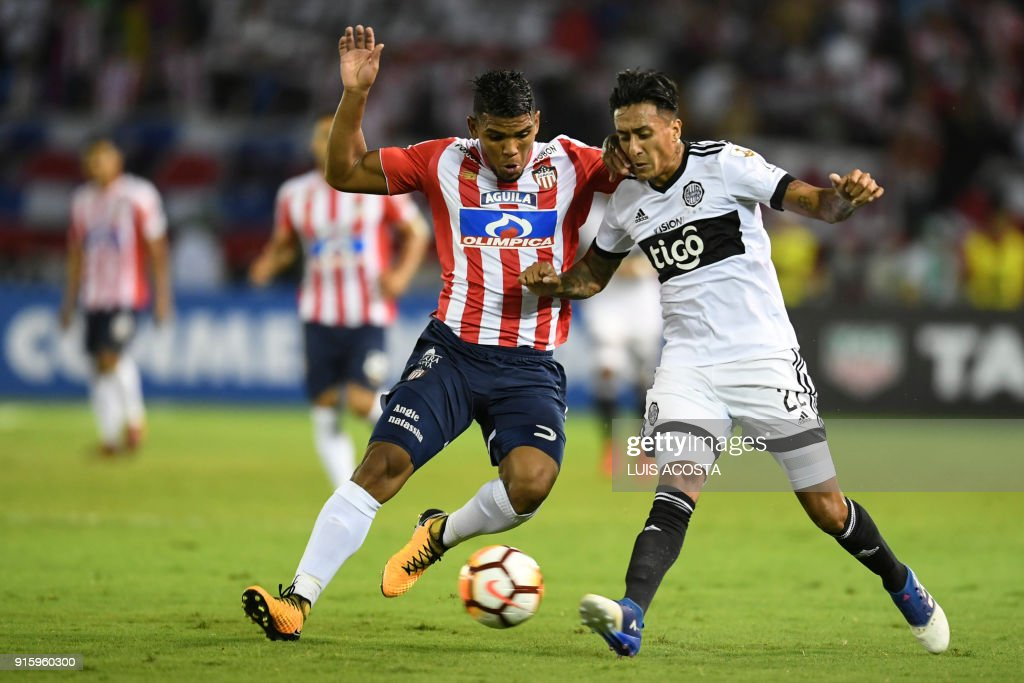 Paraguay's Olimpia midfielder Santiago Rosales (R) of Argentina vies for the ball with Colombian Junior defender Rafael Perez during their Copa Libertadores football match at Roberto Melendez stadium in Barranquilla, Colombia, on February 8, 2018. / AFP PHOTO / Luis ACOSTA