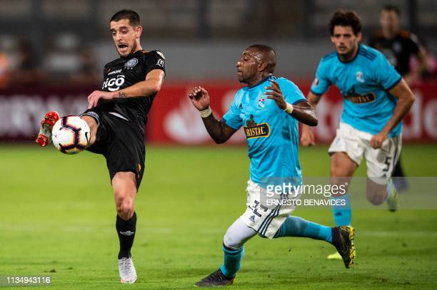 Paraguay's Olimpia player Alejandro Silva vies for the ball with Jair Cespedes of Peru's Sporting Cristal during a Libertadores Cup football match at...