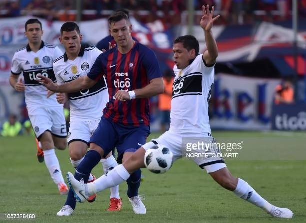 Paraguay's Olimpia player Jose Leguizamon vies for the ball with Cerro Porteno's Diego Churin during the Paraguayan Clausura football tournament...
