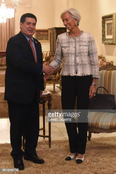 Paraguay's President Horacio Cartes and IMF Managing Director Christine Lagarde shake hands during a meeting at the Muruvicha Roga presidential...