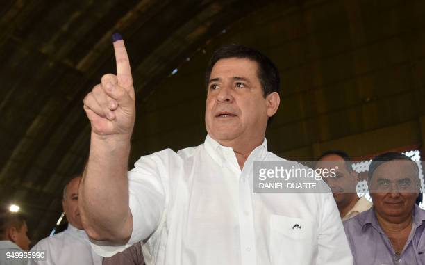 Paraguay's President Horacio Cartes shows his inked finger after voting in Asuncion on April 22 during Paraguay's presidential election Opinion polls...