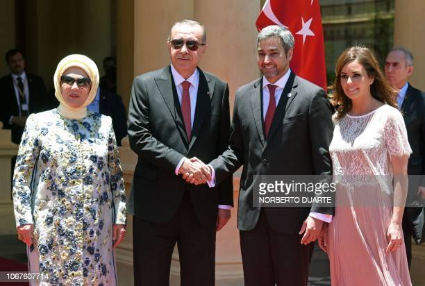 Paraguay's President Mario Abdo Benitez and Turkey's President Recep Tayyip Erdogan shake hands flanked by First Ladies Silvana Lopez and Emine...