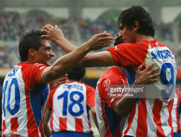 Paraguay's Roque Santa Cruz is congratulated by teammate Roberto Acuna after scoring off a header in the 38th minute 02 June 2002 during their Group...