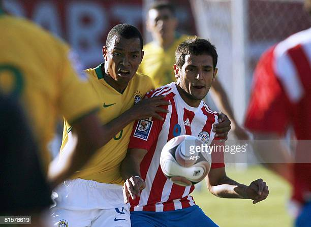 Paraguay's Roque Santa Cruz struggles for the ball with Brazil's Gilberto Silva during their FIFA World Cup South Africa2010 qualifier football match...