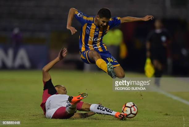 Paraguay's Sportivo Luqueno player Blas Armoa leaps over Ecuador's Deportivo Cuenca Facundo Melivillo during their Copa Sudamericana 2018 football...