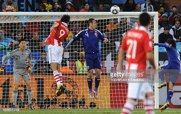 Paraguay's striker Roque Santa Cruz heads the ball in front of Japan's goal defended by goalkeeper Eiji Kawashima and Japan's defender Marcus Tulio...