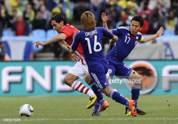 Paraguay's striker Roque Santa Cruz is challenged for the ball by Japan's midfielder Makoto Hasebe and Japan's striker Yasuhito Okubo during the 2010...