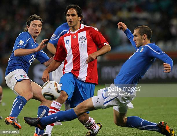 Paraguay's striker Roque Santa Cruz is tackled by Italy's defender Giorgio Chiellini during the Group F first round 2010 World Cup football match...