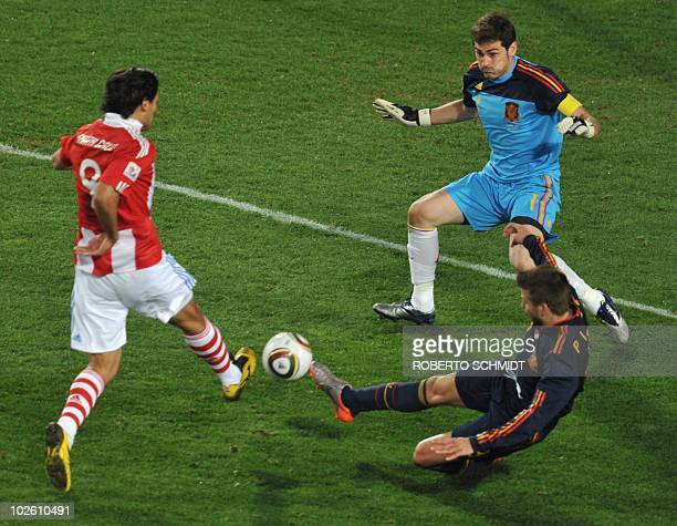 Paraguay's striker Roque Santa Cruz tries for a chance on goal but his shot is saved by Spain's goalkeeper Iker Casillas as Spain's defender Gerard...