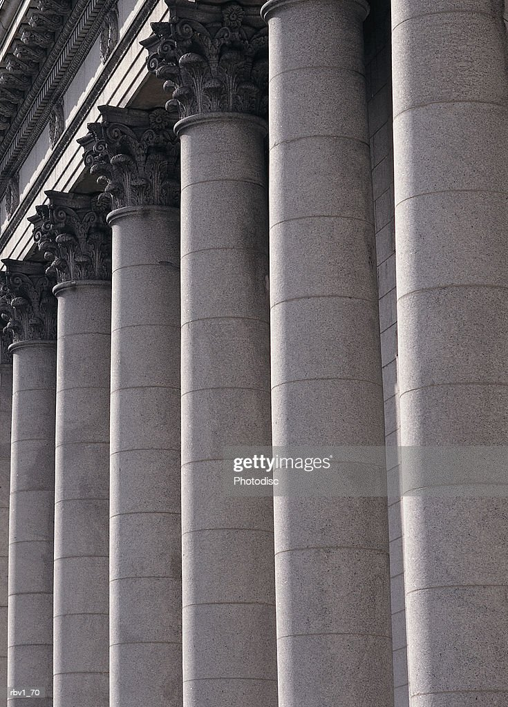 parallel stone columns line the side of an old building : Foto de stock