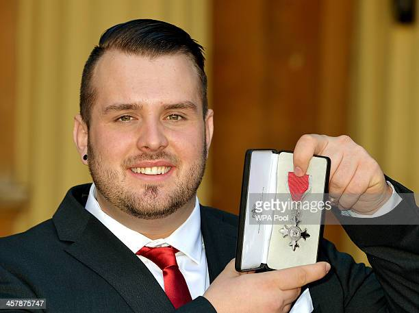 Paralympic discus Gold Medallist Aled Davies holds his MBE after it was presented to him by the Prince of Wales at an Investiture ceremony at...