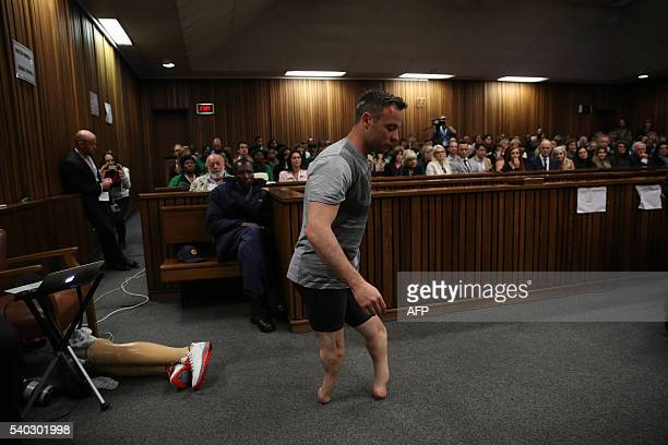 TOPSHOT Paralympic gold medalist Oscar Pistorius prepares to walk across the courtroom without his prosthetic legs during the third day of his...