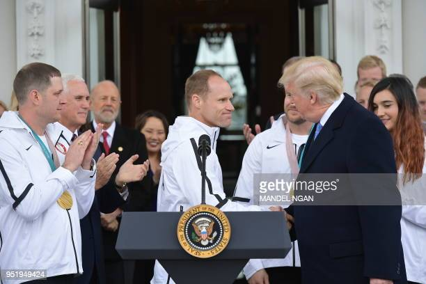Paralympic medalist skiier Dan Cnossen reacts as US President Donald Trump shakes his hand during an event honoring the US Olympic team in the North...