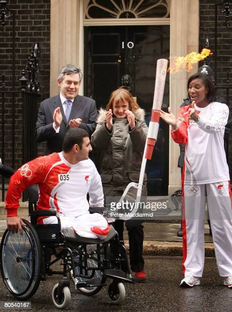 paralympic powerlifter Ali Jawad takes the Olympic torch from Athlete Denise Lewis in Downing Street accompanied by Prime Minister Gordon Brown and...