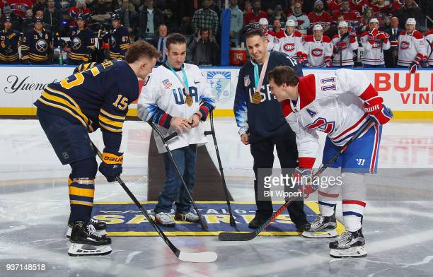 Paralympic Sled Hockey Gold Medalists Adam Page and Luke McDermott take part in a ceremonial puck drop between Jack Eichel of the Buffalo Sabres and...