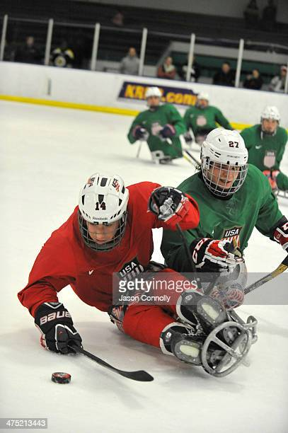 S Paralympic Sled Hockey Team athletes Daniel McCoy and Josh Pauls fight for control of a loose puck during training at the Sertich Ice Arena on...