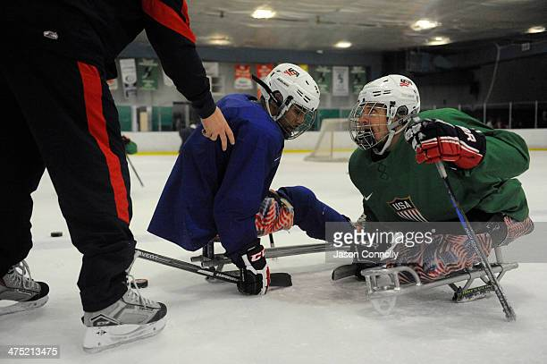 S Paralympic Sled Hockey Team athletes Greg Shaw and Rico Roman wait for the drop of the puck during a faceoff drill during practice at the Sertich...