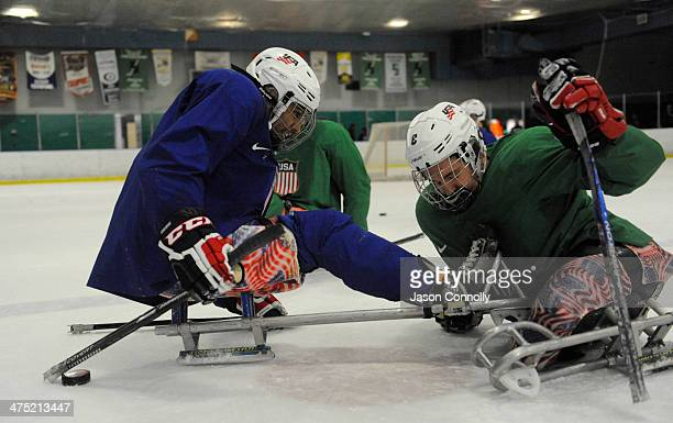 S Paralympic Sled Hockey Team athletes Rico Roman and Greg Shaw fight for the puck during a faceoff drill during practice at the Sertich Ice Arena on...