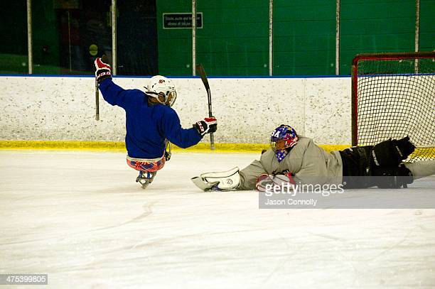 S Paralympic Sled Hockey Team goalie Jen Yung Lee dives in an attempt to stop a shot on goal during the team's final US based practice at the Sertich...