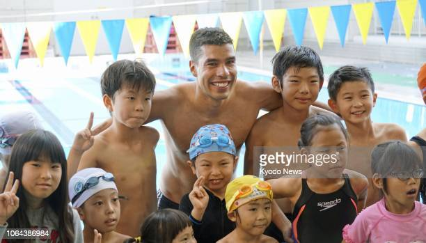 Paralympic swimmer Daniel Dias of Brazil poses for a photo with children in Tokyo on Nov 23 2018 Dias has won 14 swimming gold medals at the...