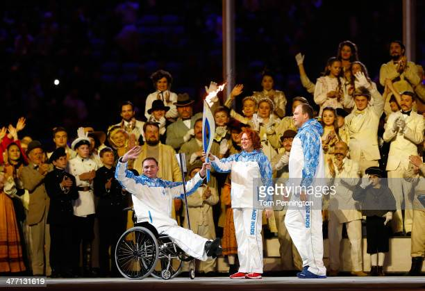 Paralympic torch bearers wave to the crowd during the Opening Ceremony of the Sochi 2014 Paralympic Winter Games at Fisht Olympic Stadium on March 7...