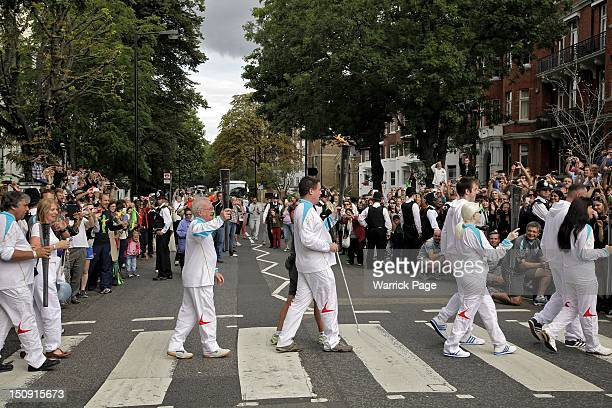 Paralympic Torchbearers Chris Tattersall Ken Maidens Graham Helm Ketaki Vaidya and Lucy Priest carry Paralympic torches across the Abbey Road...