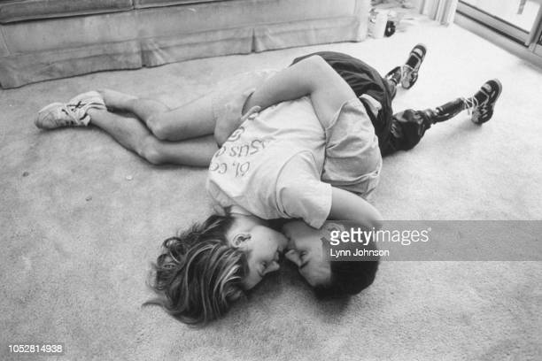 Casual portrait of double amputee and runner Aimee Mullins embracing and kissing her boyfriend Eric Treiber on living room floor at home Prosthetic...