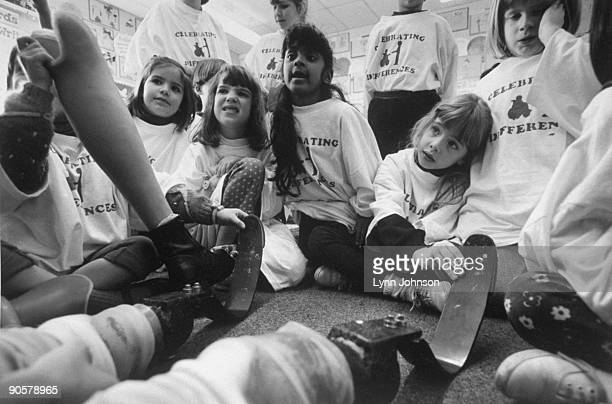 Portrait of several young girls with double amputee and runner Aimee Mullins during show tell with her artificial legs in classroom View of girls...