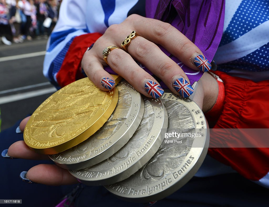 Paralympics GB swimmer Heather Frederiksen holds her gold and silver medals during the London 2012 Victory Parade for Team GB and Paralympics GB athletes on September 10, 2012 in London, England.