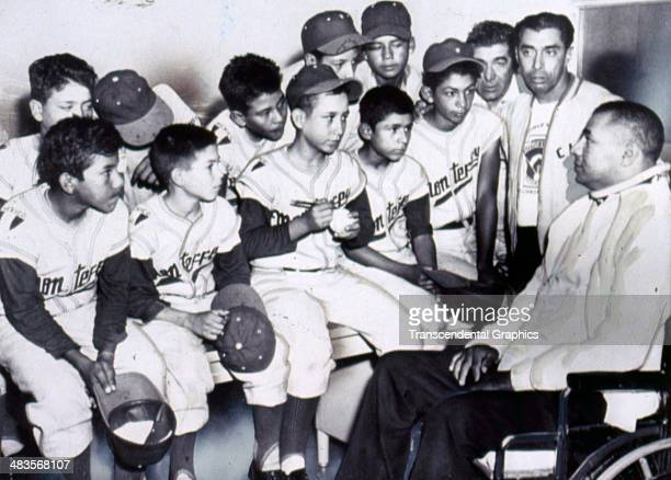 Paralyzed Brooklyn Dodger catcher Roy Campanella meets with a group of Puerto Rican little leaguers in 1958 in Brooklyn New York