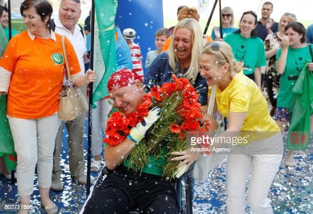 Paralyzed Ukrainian Oleg Ivanenko celebrates as he sets a unique world triathlon record, at the Olimpiyskiy stadium in Kiev, Ukraine, on June 28,...