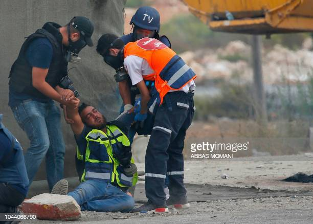 TOPSHOT A paramedic and journalists help a fellow journalist affected by tear gas fired by Israeli forces during clashes near the Israeli settlement...