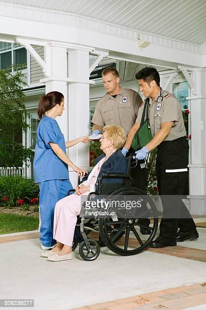 Rettungssanitäter und Krankenschwester im Gespräch mit senior Frau im Rollstuhl