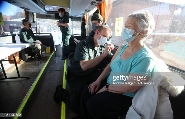 Paramedic Andrew Parker gives the vaccine to Elizabeth and Sandy Robertson inside a holiday coach outside Culloden Medical Practice near Inverness,...