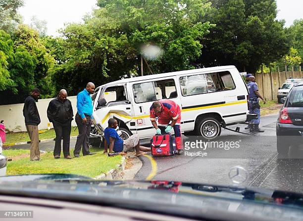 Paramedic attending injured passenger after minibus taxi accident