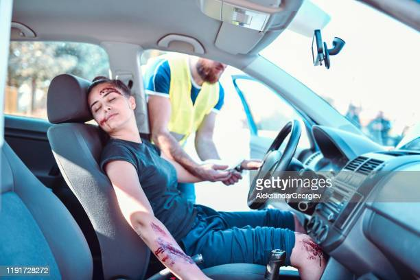 paramedic checking female's pulse after car accident - gory car accident photos stock pictures, royalty-free photos & images
