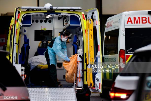 Paramedic cleans inside an ambulance parked outside Guy's Hospital in London on December 29 as a new strain of the coronavirus appears to be behind...