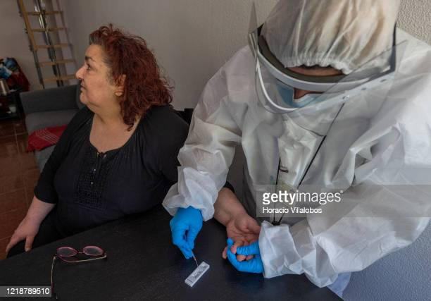 A paramedic collects capillary blood after pricking Cascais resident Rosario Sezero while testing residents at their homes for coronavirus infections...