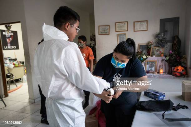 Paramedic from the Calafia group places tape on his partner's gloves on July 28, 2020 in La Paz, Mexico. Many Mexican States remain in orange...