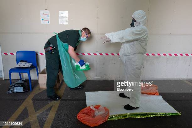 A paramedic from the South Central Ambulance Service operated by South Central Ambulance Service NHS Foundation Trust is guided through the removal...
