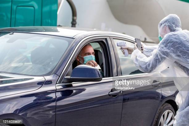 paramedic health control on the international borders taking pictures of passanger traveling across the country - infrared thermometer stock pictures, royalty-free photos & images