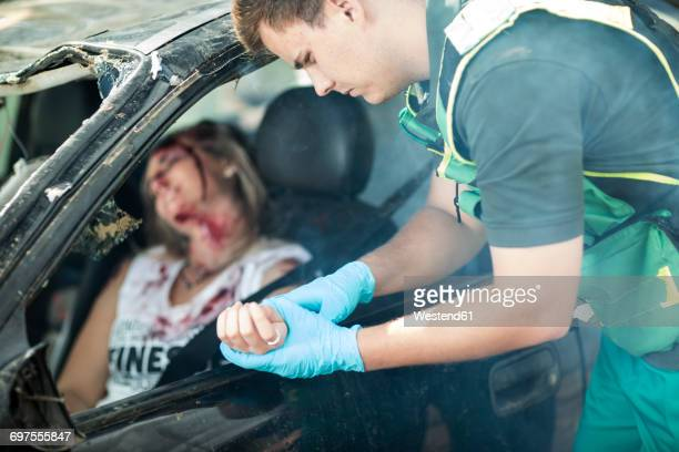 paramedic helping car crash victim after accident - bloody car accidents stock pictures, royalty-free photos & images