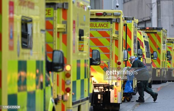 Paramedic is seen by a line of ambulances outside the Royal London Hospital in east London on January 5, 2021. - England's six-week lockdown, which...