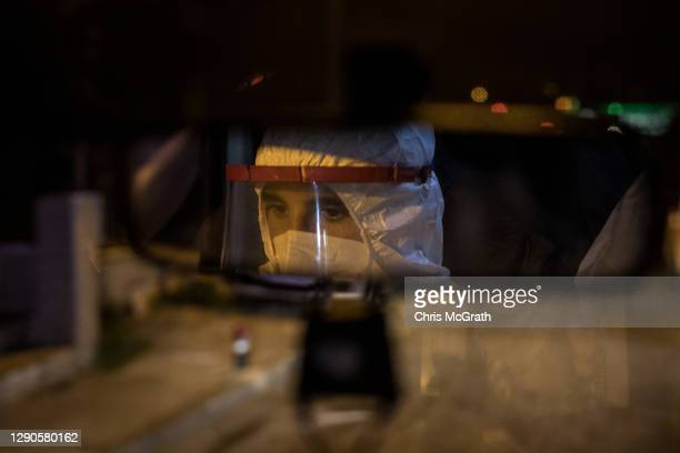 Paramedic is seen in the rearview mirror of an ambulance as they transport a Covid-19 positive patient to a hospital on December 10, 2020 in...