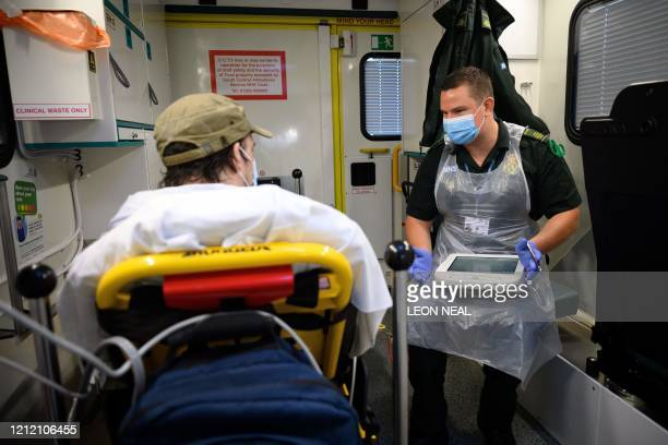 Paramedic James Hansford looks on during the treatment of a patient who has previously tested positive for the COVID-19 virus for a separate issue,...