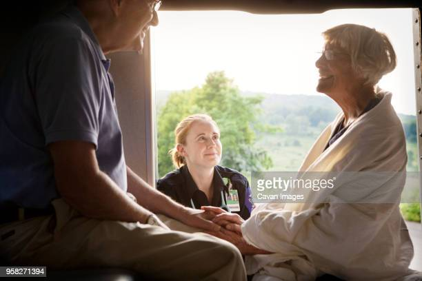 paramedic looking at patient sitting with husband in ambulance - rescue worker stock pictures, royalty-free photos & images