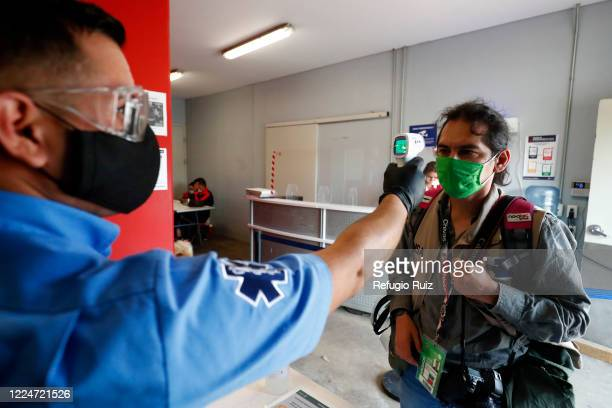 A paramedic measures the temperature to a member of the press as part of the COVID 19 protocol prior to the match between n Chivas and Atlas as part...